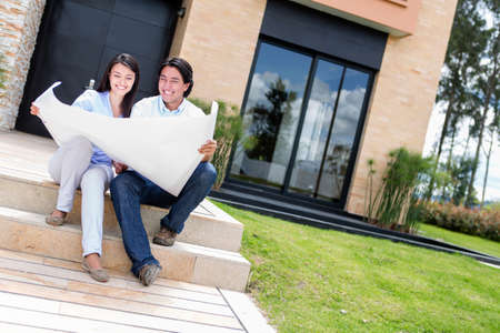Happy couple with blueprints of their home  Stock Photo - 15599790