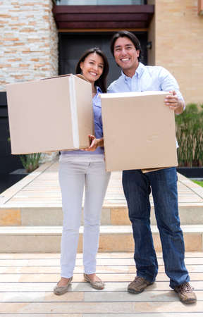 Moving couple holding boxes in front of their new house  photo