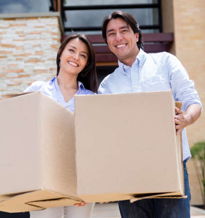 Loving couple moving house and holding cardboard boxes  Stock Photo - 15581179