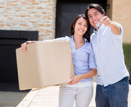 Couple moving into their new house and holding the keys  photo