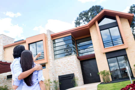 buy house: Couple looking at a beautiful house to buy  Stock Photo