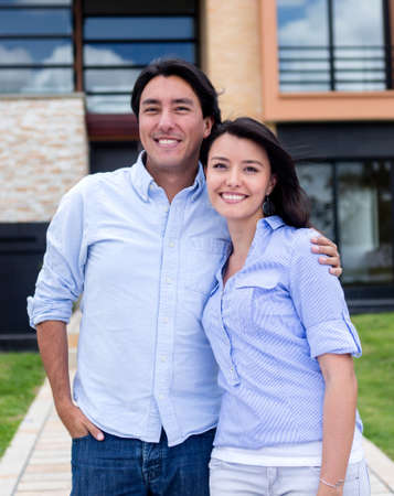Happy couple outdoors in front of their house  Stock Photo - 15599788