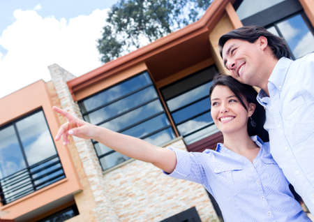 new house: Happy couple pointing away in front of their home