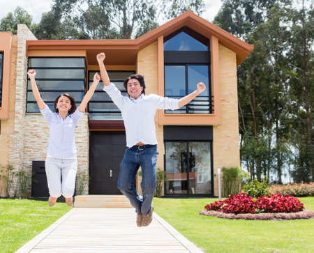couple home: Excited couple jumping after buying a house