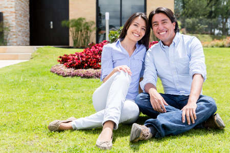 Happy couple sitting outdoors in front of their house  Stock Photo - 15599793