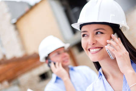 Architects talking on the phone at a building site  photo