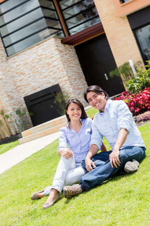 Couple looking very happy sitting in their frontyard  Stock Photo - 15783779