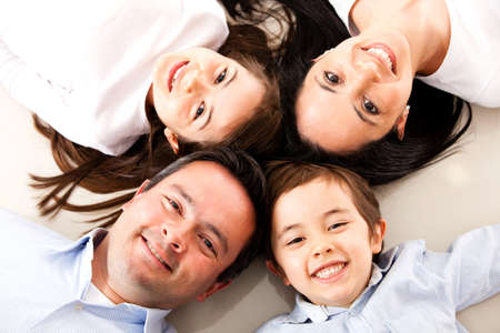 Happy family with heads together on the floor  Stock Photo - 15783804