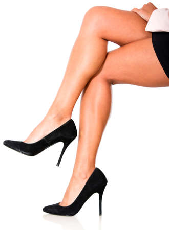 woman legs: Woman crossing legs and wearing high-heels isolated over white