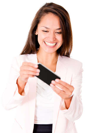 Woman playing games in her cell phone - isolated over a white background photo