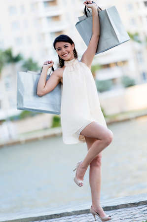 Happy shopping woman  with arms up holding bags  photo