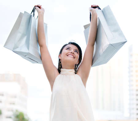 Happy female shopper with arms up holding shopping bags  photo