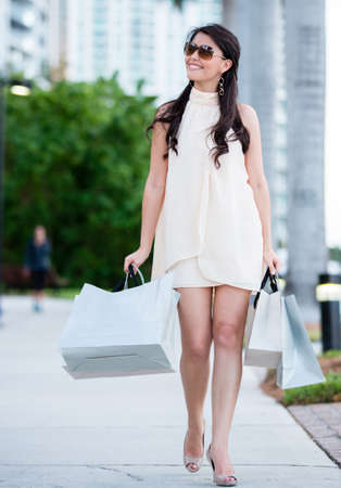 Beautiful shopping woman walking outdoors carrying bags  Stock Photo - 16057399