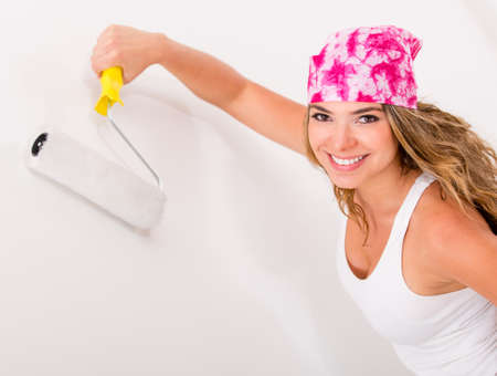 redecorating: Happy woman painting a wall redecorating her house