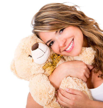 Cute woman holding a teddy bear - isolated over a white background  photo