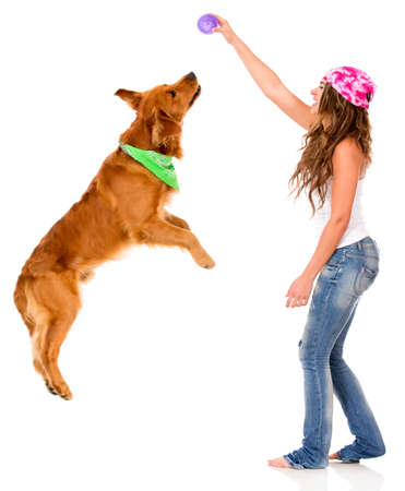 golden ball: Woman playing with her dog - isolated over a white background