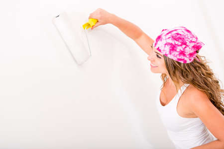 Woman painting the wall with a paint roller photo