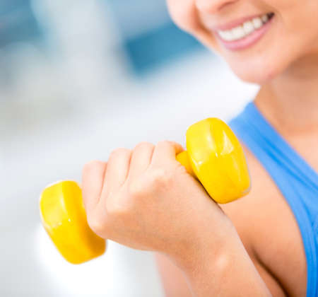 body built: Fit woman lifting weights at the gym  Stock Photo