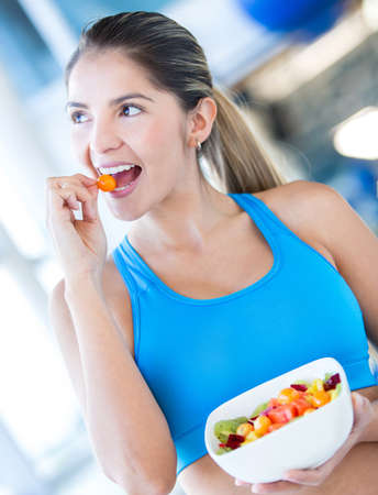 Healthy eating woman having a fruit salad at the gym  photo