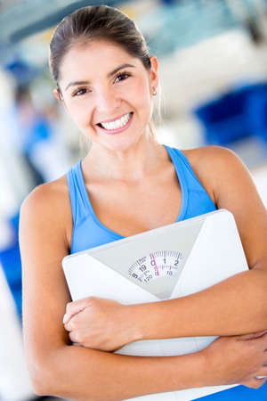 Happy gym woman holding weight scale  Stock Photo - 16307748