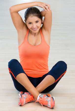 Woman at the gym stretching her arm before working out  Stock Photo - 16397901