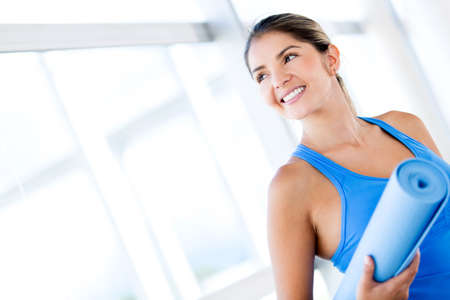 skinny woman: Beautiful woman with a yoga mat at the gym Stock Photo