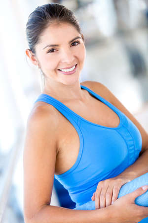 Beautiful woman at the gym holding a yoga mat  Stock Photo - 16397903