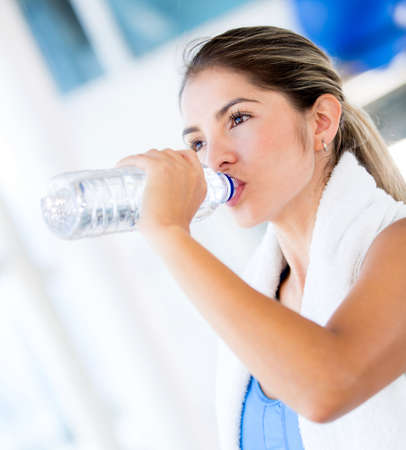 hydrate: Woman drinking water at the gym after working out  Stock Photo