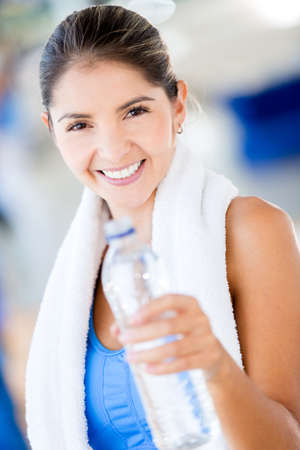 Gym woman with a bottle of water looking very happy  Stock Photo - 16397906