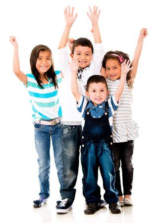nios hispanos: Emocionado grupo de ni�os con los brazos para arriba que se divierten - aislados en blanco