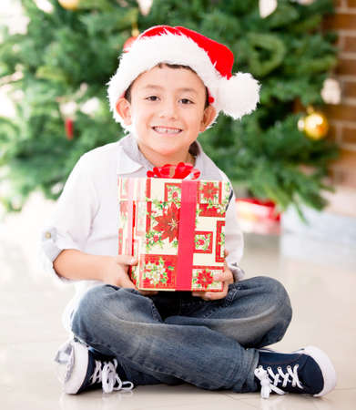Happy boy holding a Christmas gift and smiling  photo