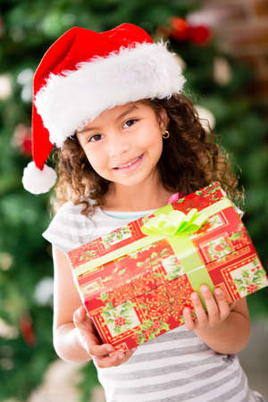 Christmas girl wearing a Santa hat and holding a present  photo