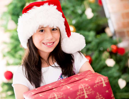 Beautiful Christmas portait of a girl holding a present  Stock Photo - 16409418