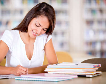 Woman studying at the library looking happy  Stock Photo - 16409408