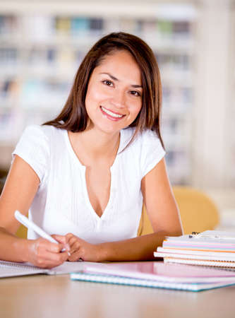 Happy university woman at the library studying  Stock Photo - 16409394