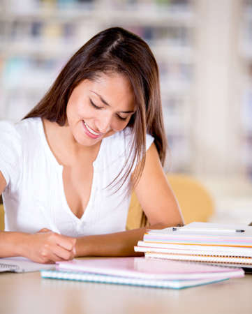 College woman studying at the library looking happy  Stock Photo - 16409390