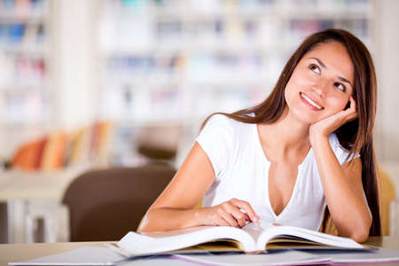 Thoughtful female student at the library looking up  Stock Photo - 16409415