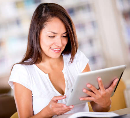 Woman at the library reading on a tablet computer  Stock Photo - 16409411