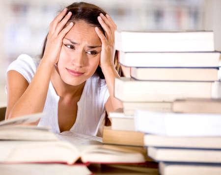 agotado: Estudiante cansado femenino en la biblioteca buscando muy frustrado