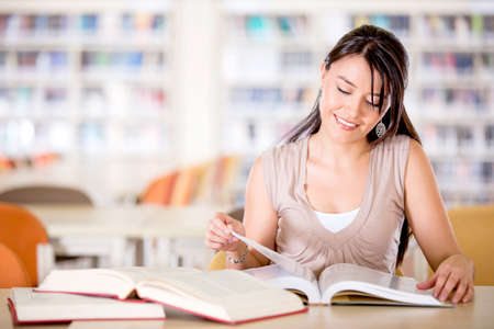 Girl at the library reading a book and smiling  Stock Photo - 16409410
