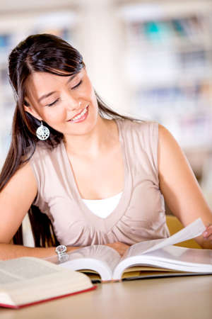 Beautiful woman reading a book at the library  Stock Photo - 16409417