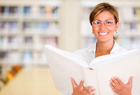 Happy librarian holding a book and smiling at the library  Stock Photo - 16454801
