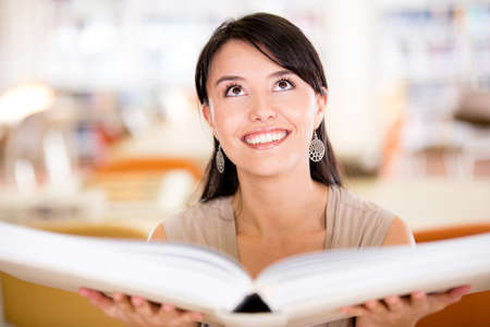 Woman with an open book at the library  photo
