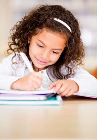 kids learning: Little girl studying at the library looking happy  Stock Photo