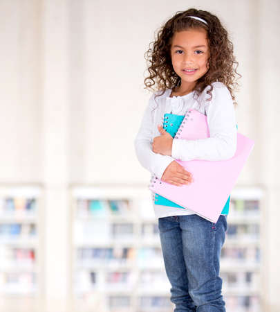 Little girl holding notebooks at the school library  Stock Photo - 16454802