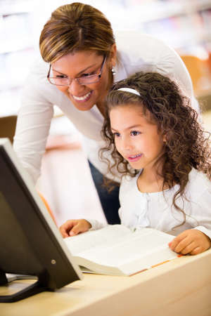 Girl at school with her teacher learning to use technology Stock Photo - 16454675