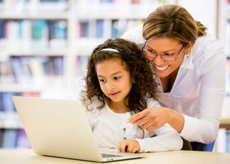 adults learning: Schoolgirl researching online with the guidance of her teacher  Stock Photo