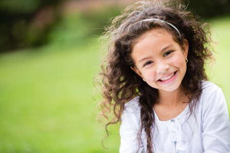 nios hispanos: Dulce al aire libre ni�a con el pelo rizado en el viento Foto de archivo