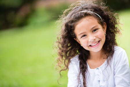 little girl smiling: Sweet little girl outdoors with curly hair in the wind  Stock Photo