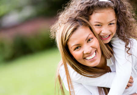 Happy mother and daughter laughing together outdoors  photo